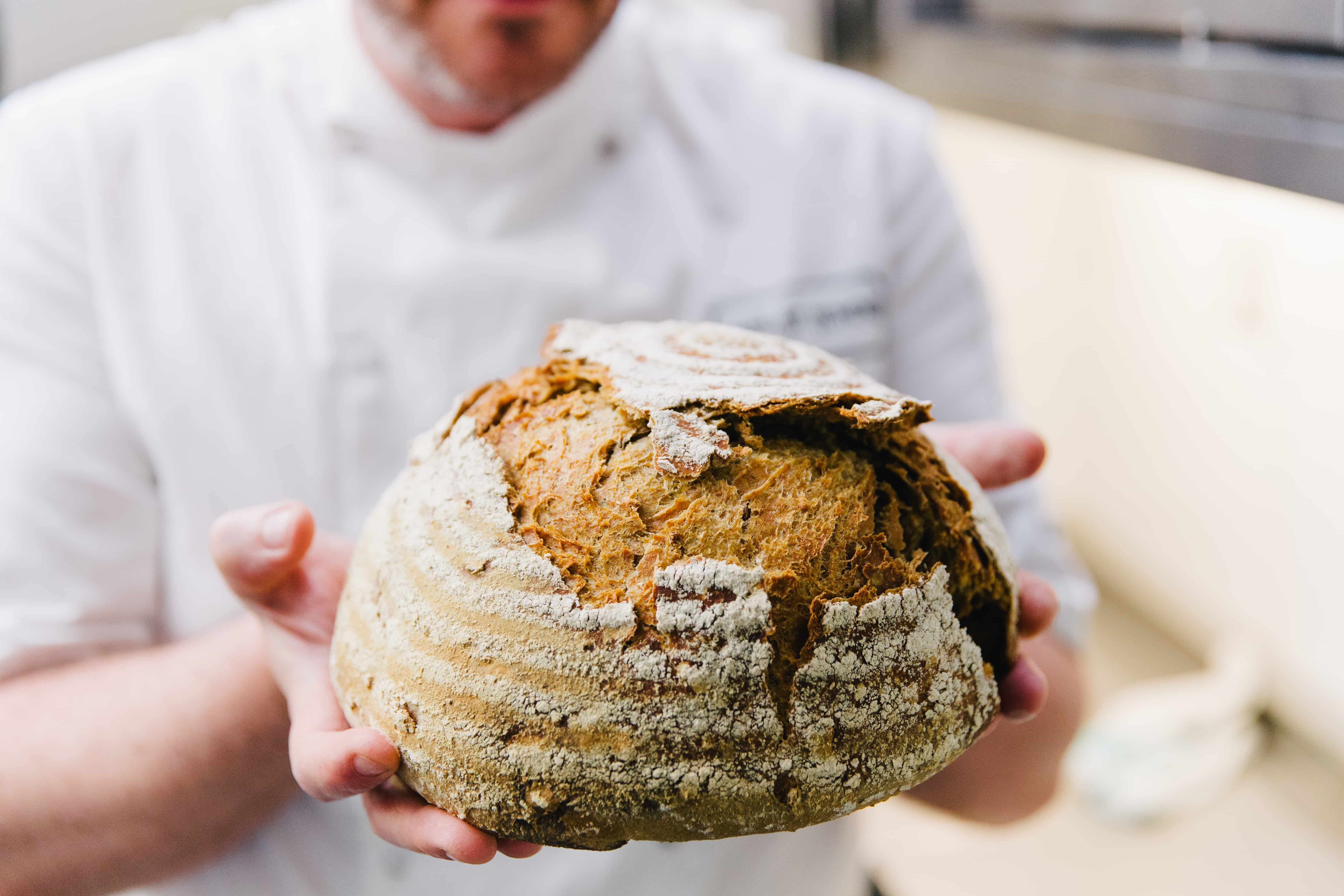 Organic bread in chef hands Cafe St Honore Organic Served Here award holder.jpg
