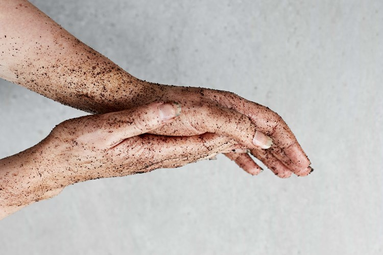 Pair of hands with exfoliating coffee scrub