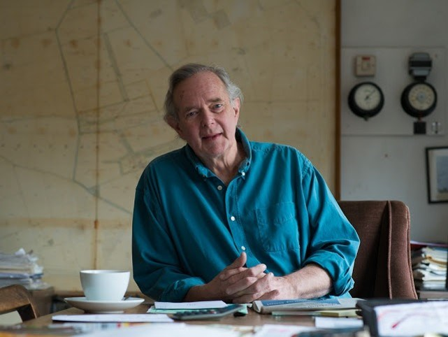 Peter Melchett sat at a desk with hands together