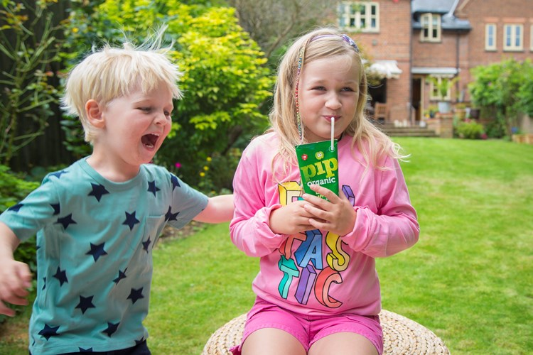 Two children in a garden, a boy and a girl - the girl is drinking a Pip Organic apple juice box