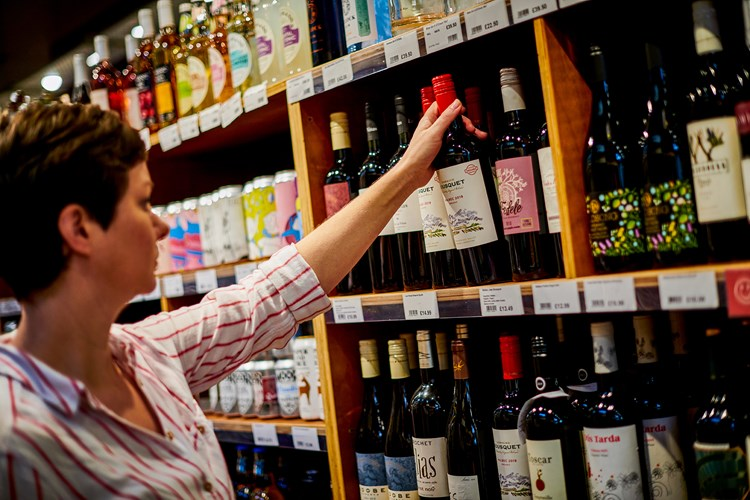 A white woman with short brown hair lifting a bottle of red wine from a wooden shelf in a store