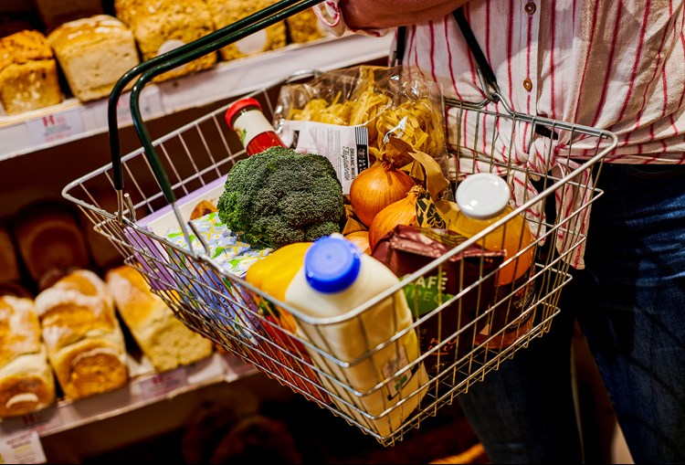 A person holding a shopping basket of food in front of a shelf of bread, with broccoli, milk, onions and other items in it