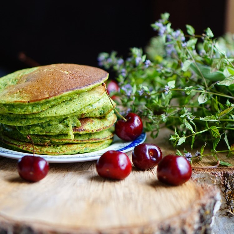pancakes on a wooden board, with cherries