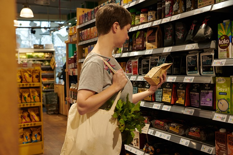 A woman with a cotton tote bag holding a bag of coffee and reading the label in an independent food shop
