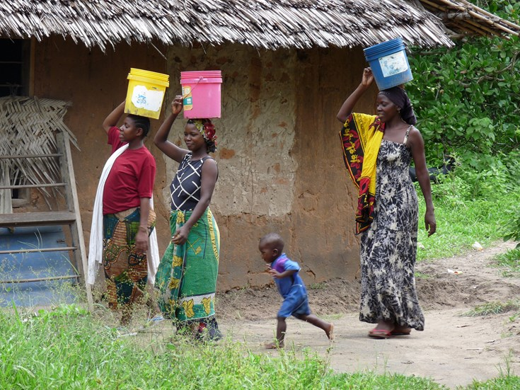 Local women return from collecting water in a community well funded using income from sustainable timber sales (pic Lodrick Mica)
